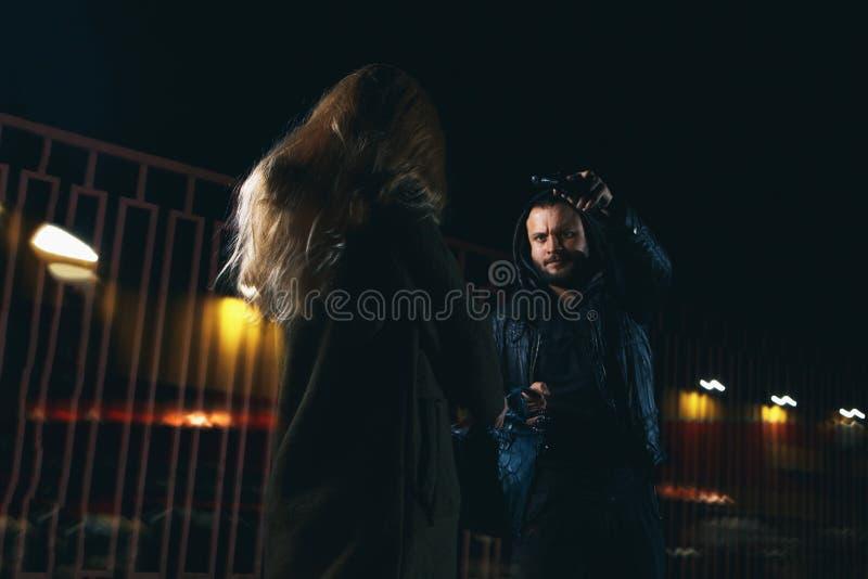 Cena da extorsão da rua da noite: homem que leva embora o saco fêmea novo fotos de stock