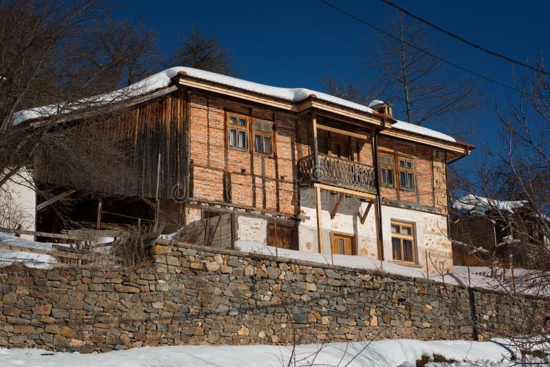 Cena da floresta do inverno Casa pequena na montanha em um dia de inverno ensolarado Conto de fadas nevado em Bulgária fotos de stock