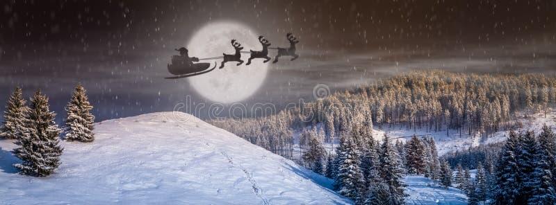 Cena da Noite de Natal com árvore, neve que cai, Santa Claus em um trenó com as renas que voam no céu fotografia de stock