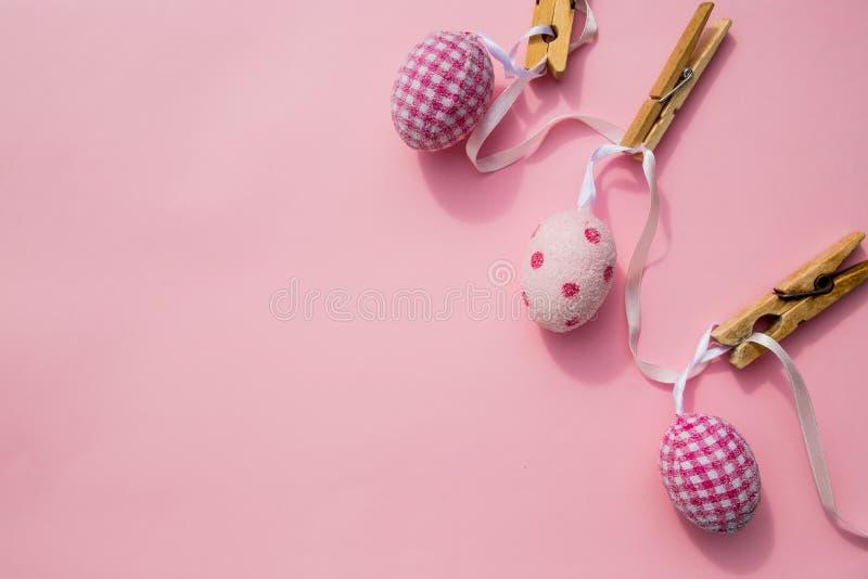 Cena da Páscoa com fileira de pendurar ovos coloridos e o pino isolados no fundo cor-de-rosa Composição feliz de easter para a mo fotografia de stock royalty free