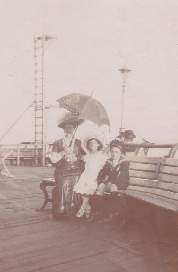 Cena da praia DT00039 - passeio da costa de mar - mãe 1900 com suas crianças fotografia de stock royalty free