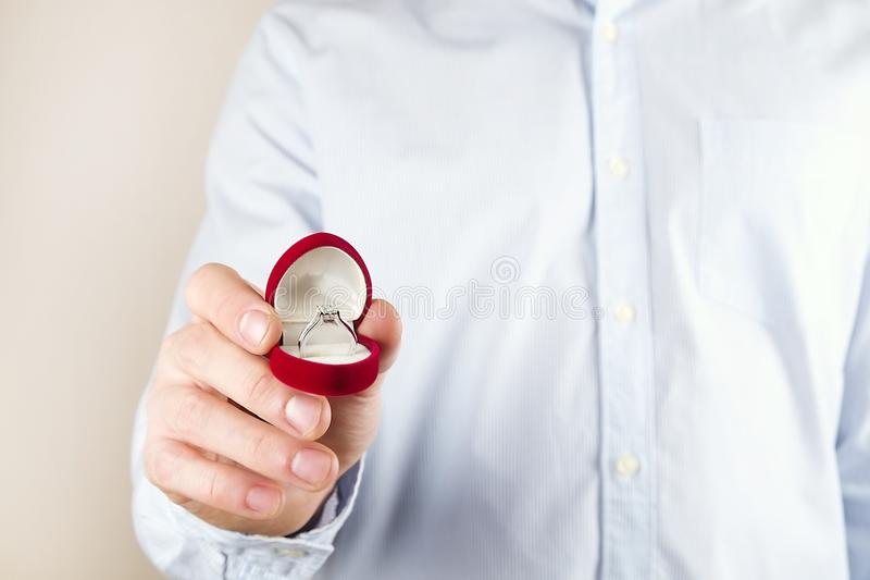 Cena da proposta do acoplamento/união/casamento Feche acima do homem que entrega o anel de diamante caro da platina do ouro a sua fotos de stock