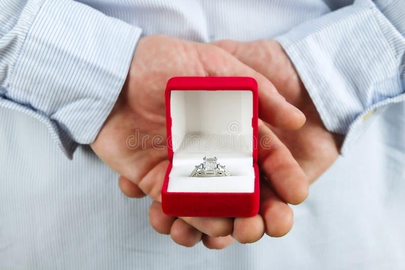 Cena da proposta do acoplamento/união/casamento Feche acima do homem que entrega o anel de diamante caro da platina do ouro a sua imagem de stock royalty free