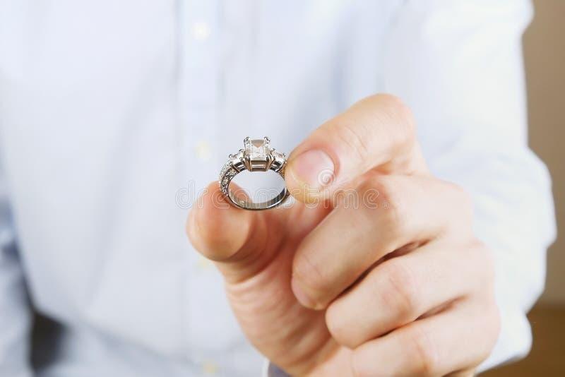 Cena da proposta do acoplamento/união/casamento Feche acima do homem que entrega o anel de diamante caro da platina do ouro a sua fotos de stock royalty free