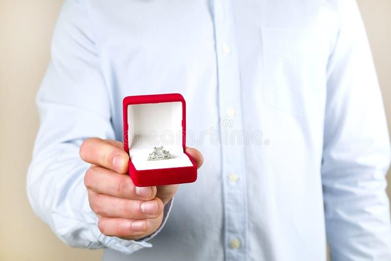 Cena da proposta do acoplamento/união/casamento Feche acima do homem que entrega o anel de diamante caro da platina do ouro a sua fotografia de stock