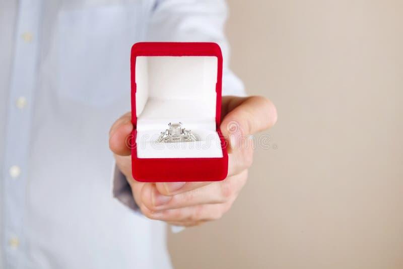 Cena da proposta do acoplamento/união/casamento Feche acima do homem que entrega o anel de diamante caro da platina do ouro a sua foto de stock royalty free
