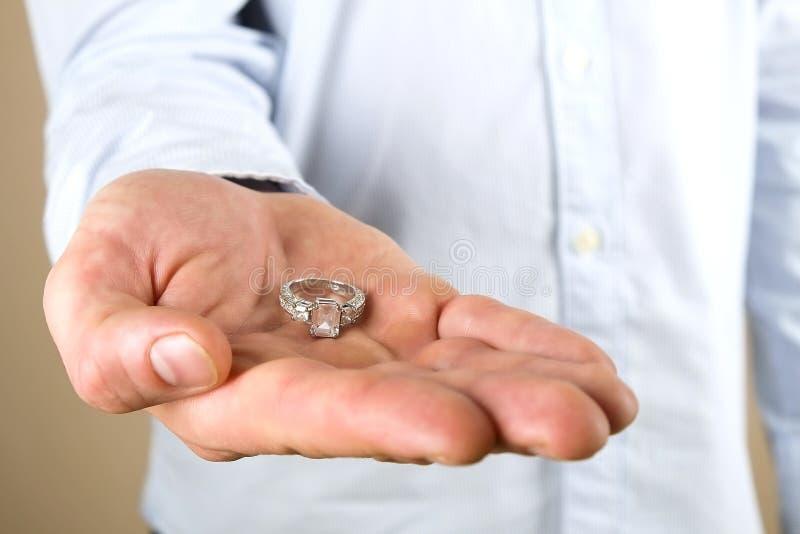 Cena da proposta do acoplamento/união/casamento Feche acima do homem que entrega o anel de diamante caro da platina do ouro a sua fotografia de stock royalty free
