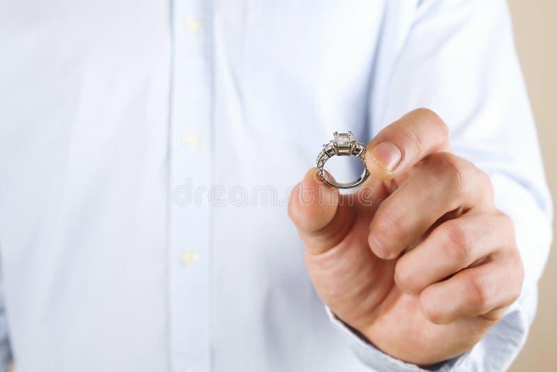Cena da proposta do acoplamento/união/casamento Feche acima do homem que entrega o anel de diamante caro da platina do ouro a sua imagens de stock royalty free