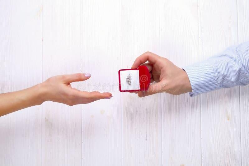 Cena da proposta do acoplamento/união/casamento Feche acima do homem que entrega o anel de diamante caro da platina do ouro a sua foto de stock