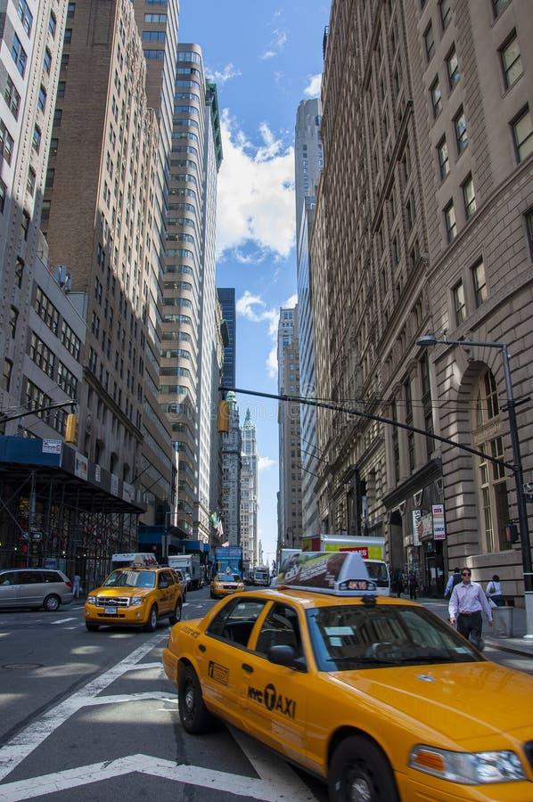 Cena da rua em New York City, com táxis amarelos em uma avenida no Lower Manhattan imagem de stock