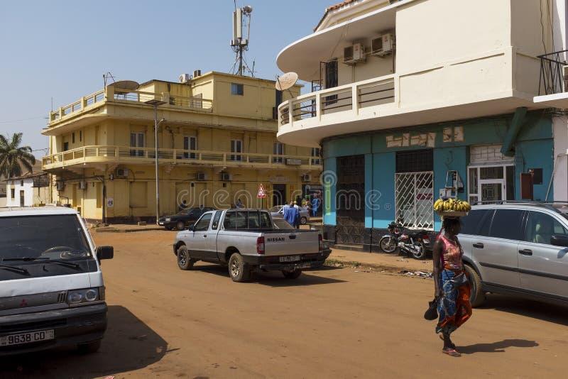 Cena da rua na cidade de Bissau com uma mulher que leva uma bandeja com as bananas em sua cabeça, em Guiné-Bissau imagens de stock royalty free
