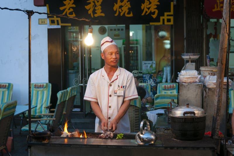 Cena da rua na cidade de Dunhuang, com um cozinheiro que prepara o no espeto do cordeiro em uma tenda do alimento, em China fotos de stock royalty free