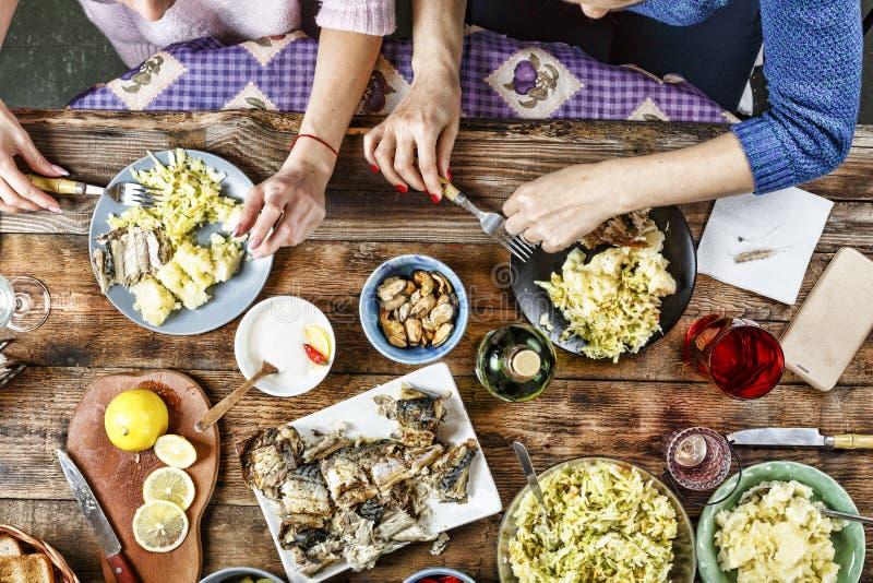 Cena de amigos Comida, consumición y concepto de familia - grupo de personas que desayuna y que se sienta en la tabla foto de archivo libre de regalías