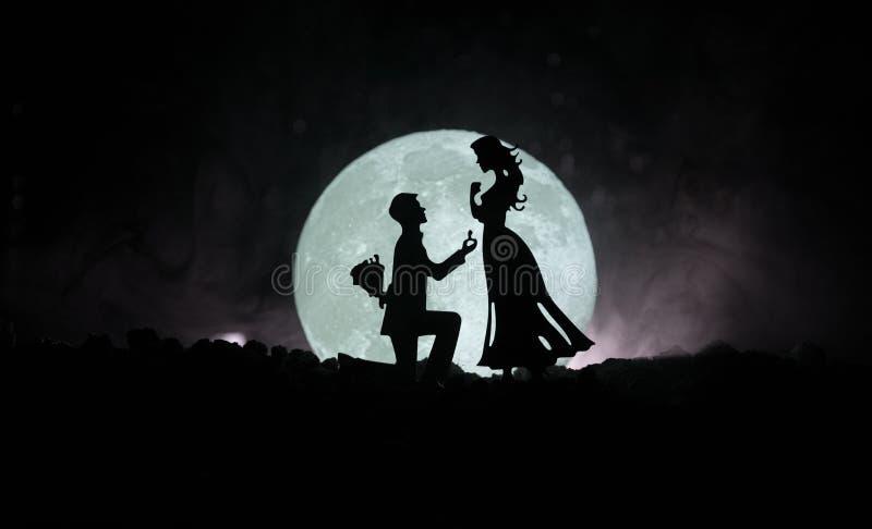 Cena de amor surpreendente Silhuetas do homem que fazem a proposta à mulher ou silhuetas dos pares contra a lua grande no fundo ilustração stock