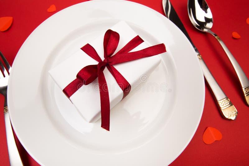 Cena de día de San Valentín con el cubierto de la tabla con el regalo, adornado con los corazones en fondo rojo Visión desde arri fotografía de archivo libre de regalías
