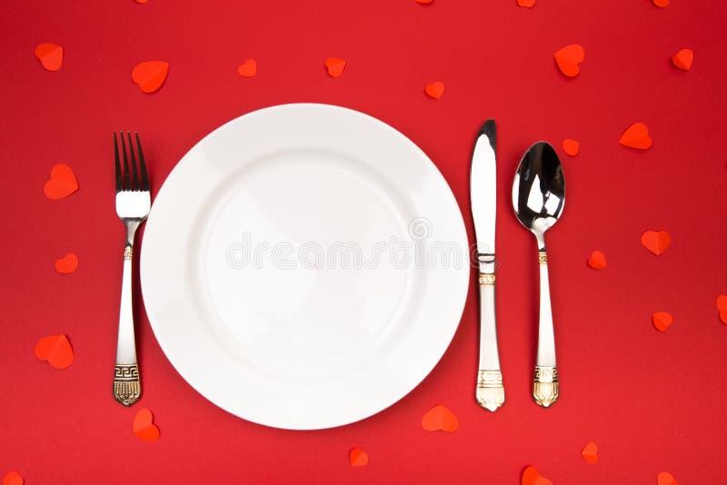 Cena de día de San Valentín con el lugar de la tabla adornado con los corazones en fondo rojo Visión desde arriba - Imagen foto de archivo
