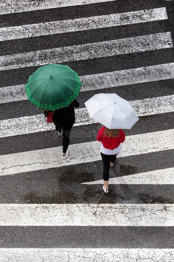 Cena de duas mulheres com o guarda-chuva da forma que cruza o passeio Vista superior foto de stock