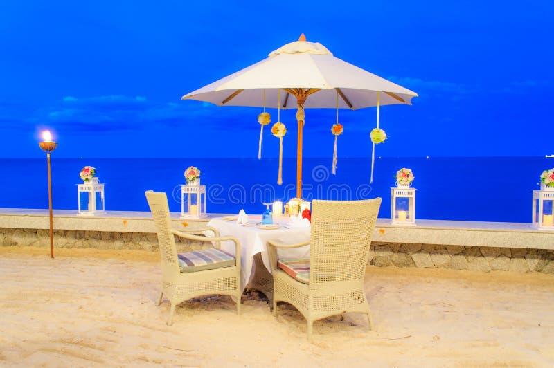 Cena de la disposición de la tabla de la luna de miel en la playa imagenes de archivo