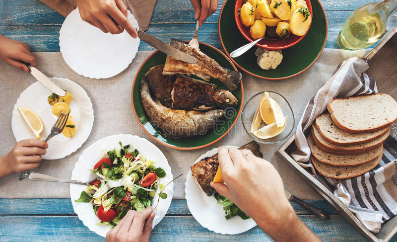 Cena de la familia con los pescados, la patata y la ensalada fritos imagen de archivo
