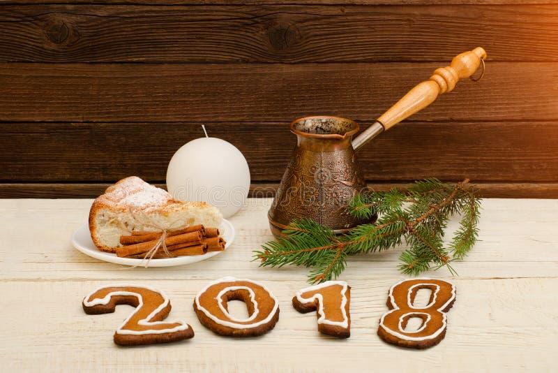 Cena de la Navidad, la figura en 2018 del pan de jengibre, empanada spruce de la rama, de la vela, del capuchino y de manzana en  fotos de archivo