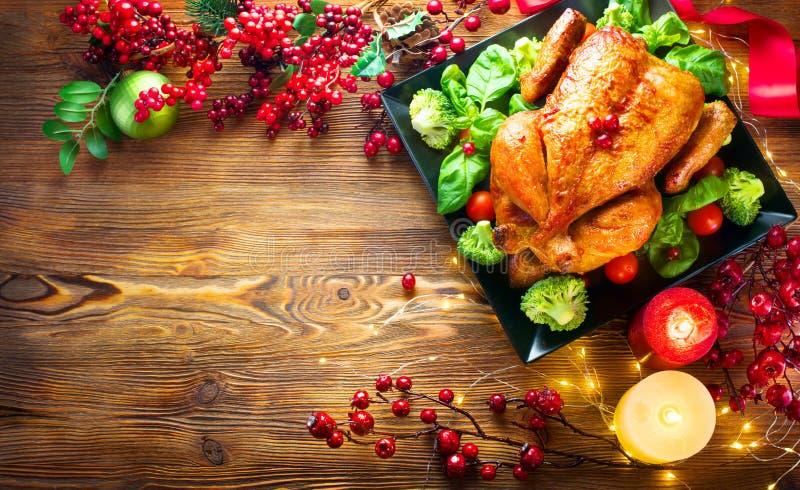Cena de la Navidad Pollo asado en la tabla del día de fiesta, adornada con las bayas, las velas y las guirnaldas Turquía asada imagenes de archivo