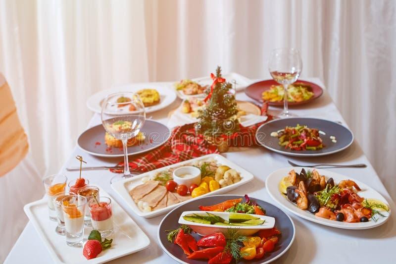 Cena de la Navidad Una tabla en el restaurante, sirvió para el peop dos imagenes de archivo