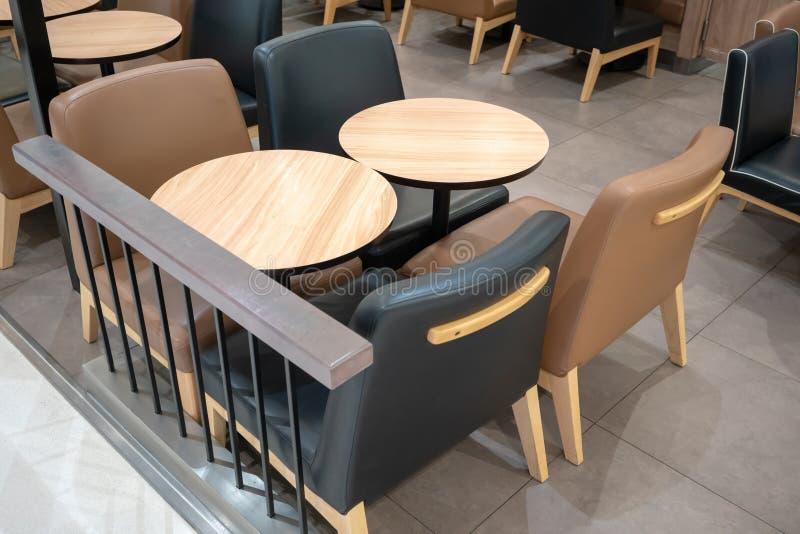 Cena de la tabla de madera con las sillas de cuero negras y marrones para cenar imagen de archivo