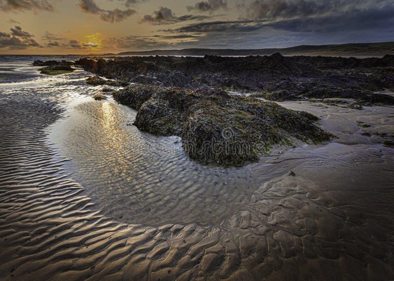Cena de sol na bela praia rochosa em Freshwater West, na costa de Pembrokeshire, no sul de Gales, Reino Unido imagem de stock royalty free