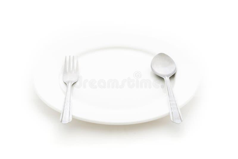 Cena del cubierto. Una placa blanca con la bifurcación y la cuchara de plata fotografía de archivo