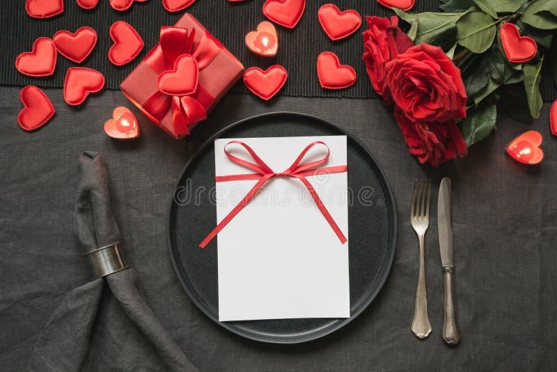 Cena del día o del cumpleaños de la tarjeta del día de San Valentín Ajuste de la tabla de la elegancia con la rosa roja en mantel fotos de archivo libres de regalías
