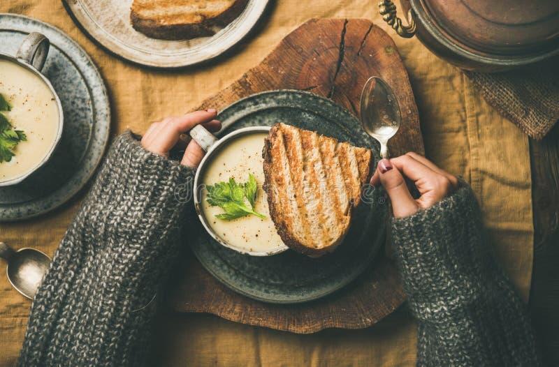 Cena del otoño o del invierno con la sopa de la crema del apio en tazas foto de archivo