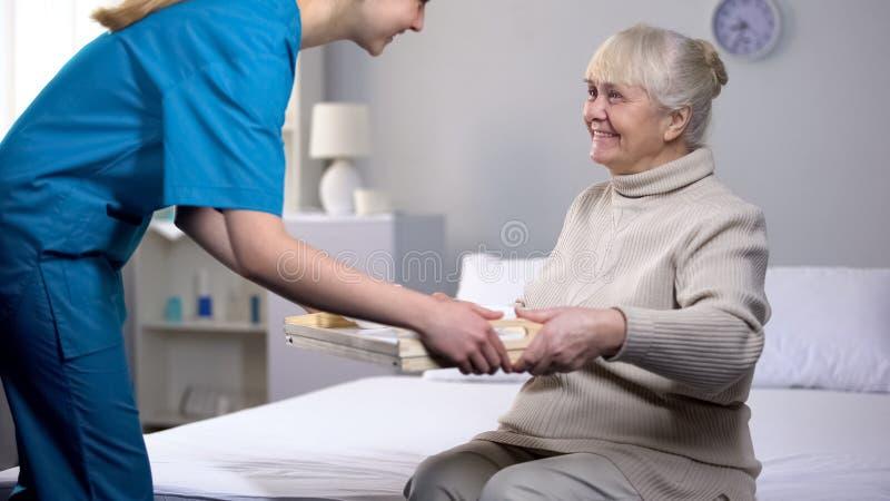 Cena del servizio del lavoratore medico al paziente femminile anziano, prendente cura della nonna immagini stock
