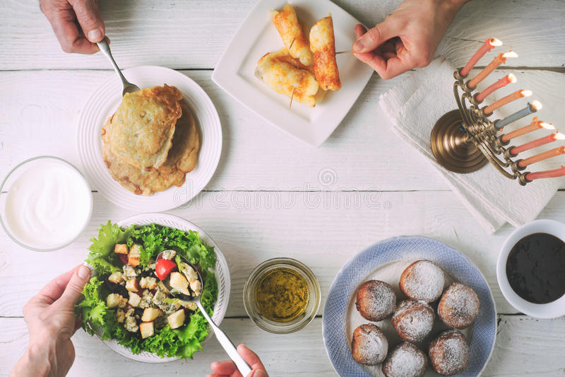 Cena di Chanukah con i piatti tradizionali sulla tavola di legno bianca immagini stock libere da diritti