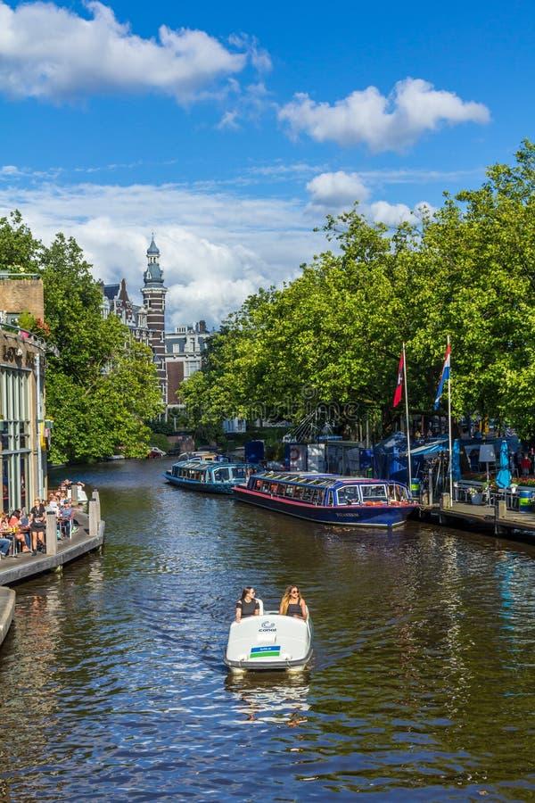 Cena do canal de Amsterdão com um barco de pá fotografia de stock royalty free
