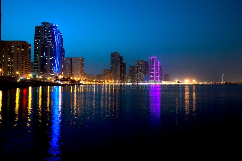 A cena do centro da noite de Sharjah com cidade ilumina-se, a elevação nova luxuosa - cidade da tecnologia em Médio Oriente imagem de stock