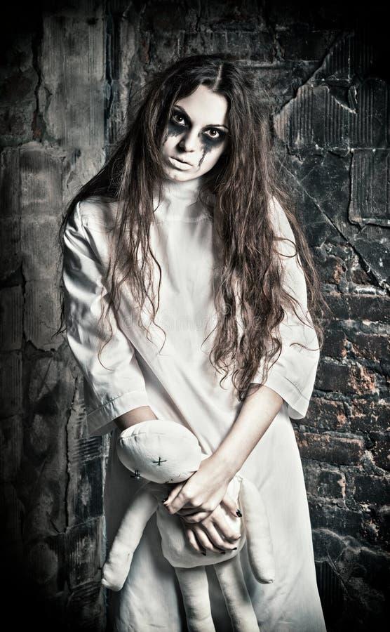 Cena do horror: menina misteriosa estranha com a boneca do moppet nas mãos fotografia de stock royalty free