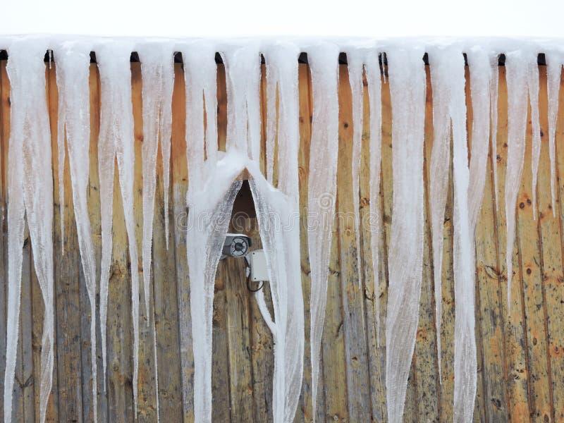 Cena do inverno - sincelos e câmara de vídeo do controle no telhado da casa da montanha imagem de stock