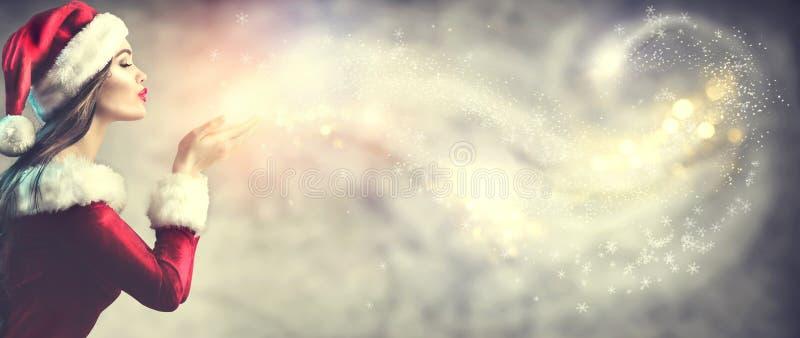Cena do Natal Jovem mulher moreno da beleza na neve de sopro do traje do partido de Santa imagem de stock