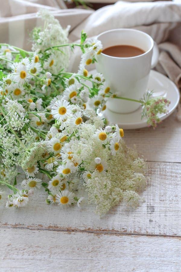 Cena do verão com uma xícara de café e umas flores selvagens imagem de stock royalty free