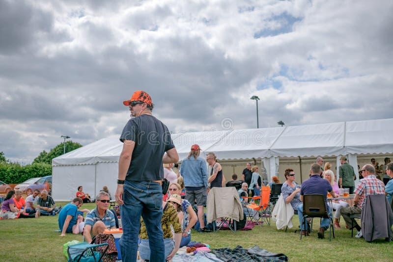 Cena exterior de um festival de música ao vivo que mostra grupos de famílias fora de um grande famoso no verão fotos de stock