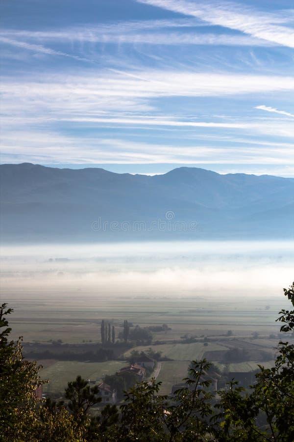 Cena idílico da manhã do vale na névoa, névoa com betwe da montanha foto de stock