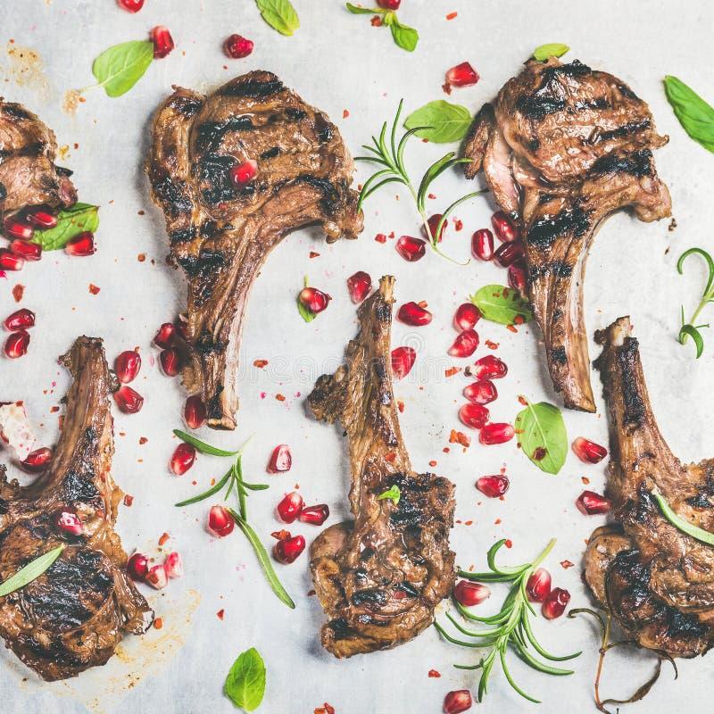 Cena lenta dell'alimento con le costole arrostite dell'agnello ed il melograno, erbe immagini stock
