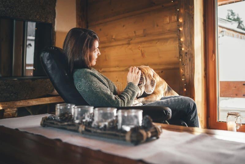 Cena macia com mulher e seu cão do lebreiro na cadeira confortável oposto à janela grande na casa acolhedor do país Férias do cam foto de stock royalty free