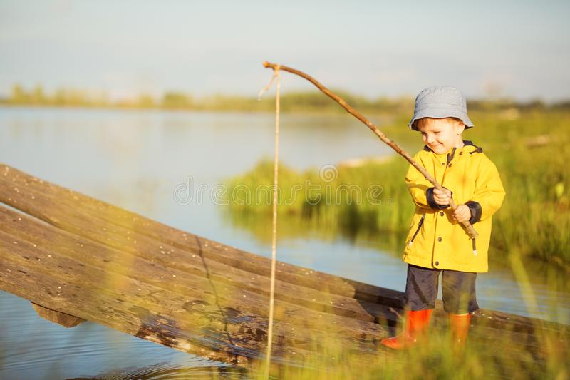 Cena pitoresca da pesca bonito do rapaz pequeno da doca de madeira no lago m?gico no dia de ver?o ensolarado, cores v?vidas fotos de stock royalty free
