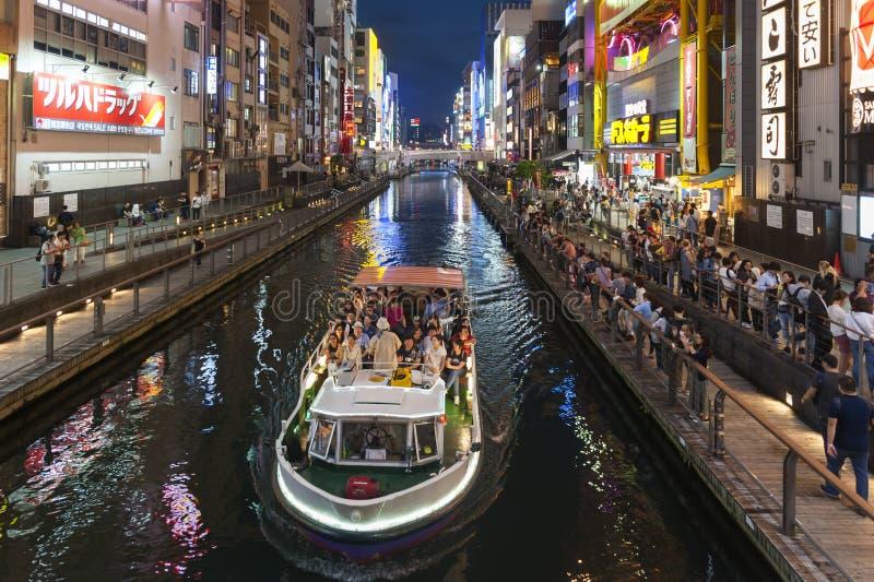 Cena popular da compra da noite do turista em Osaka City na área de Dotonbori Namba com sinais de néon e os quadros de avisos ilu fotografia de stock royalty free