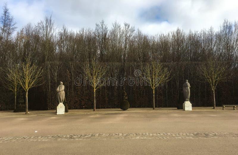 Cena quieta do inverno de árvores desencapadas e de estátuas envolvidas nas terras de Versalhes em janeiro imagem de stock royalty free