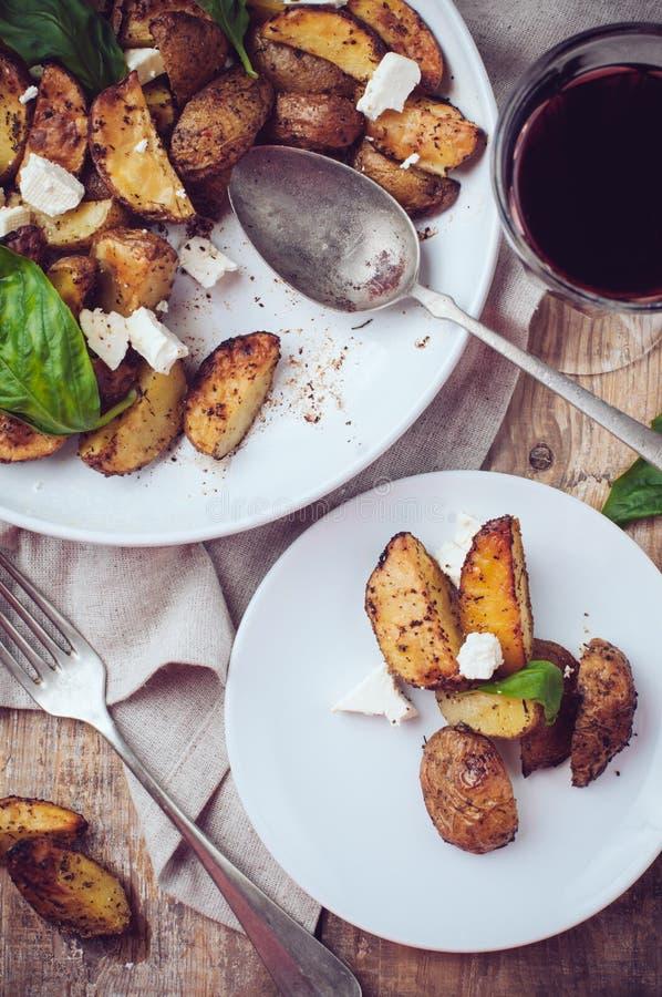 Cena rústica hecha en casa: un vidrio del vino y de una patata cocida imagen de archivo