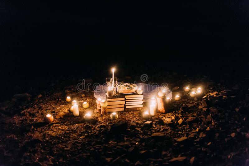 Cena romantica con le candele, le lanterne ed i vetri di vino alla costa contro la notte meravigliosa immagini stock libere da diritti