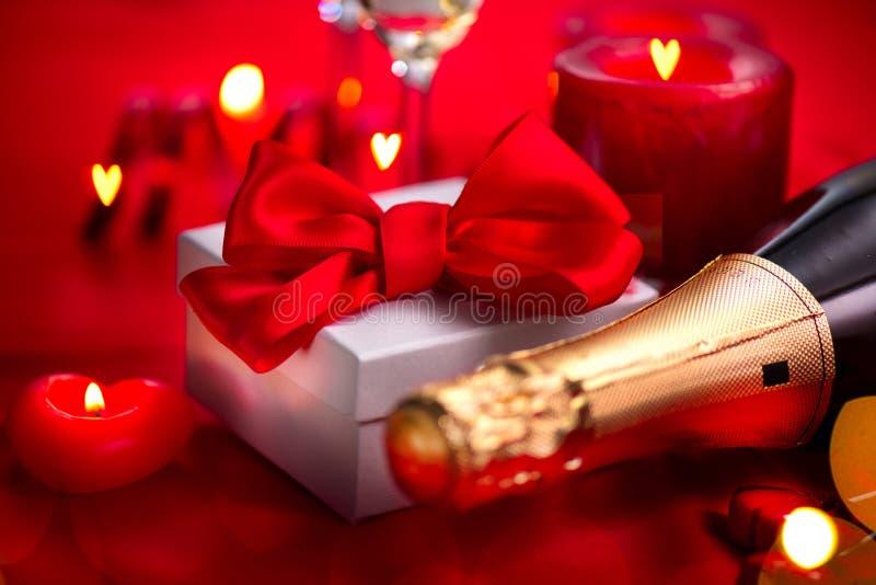 Cena romantica di giorno di biglietti di S. Valentino data Champagne, candele e contenitore di regalo sopra il fondo di rosso di  fotografia stock
