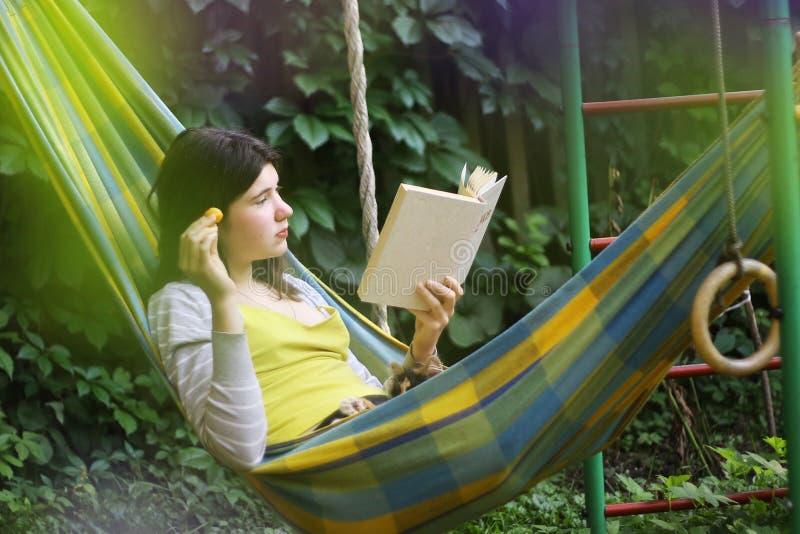 Cena sereno com a menina adolescente na rede com o livro de leitura do abricó fotografia de stock royalty free